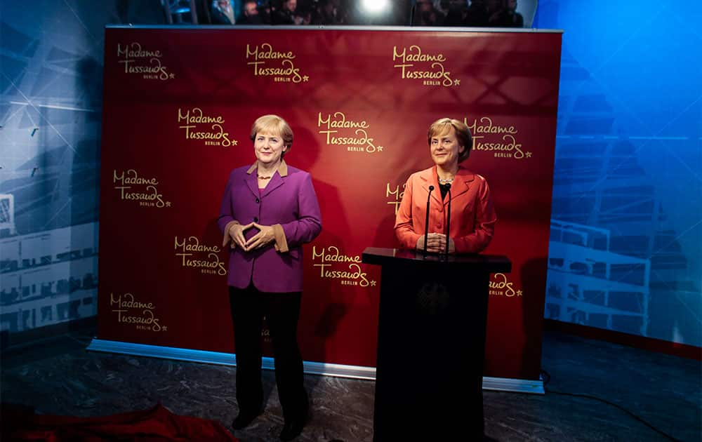 A new wax figure of German Chancellor Angela Merkel, left, is presented to the media next to a wax figure from 2005, right, at Madame Tussauds in Berlin, Germany.