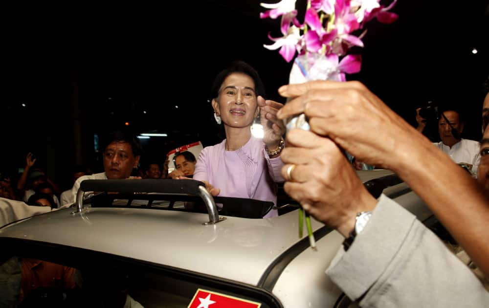 Myanmar opposition leader Aung San Suu Kyi receives flowers upon her arrival at Yangon International Airport after returning from Europe.