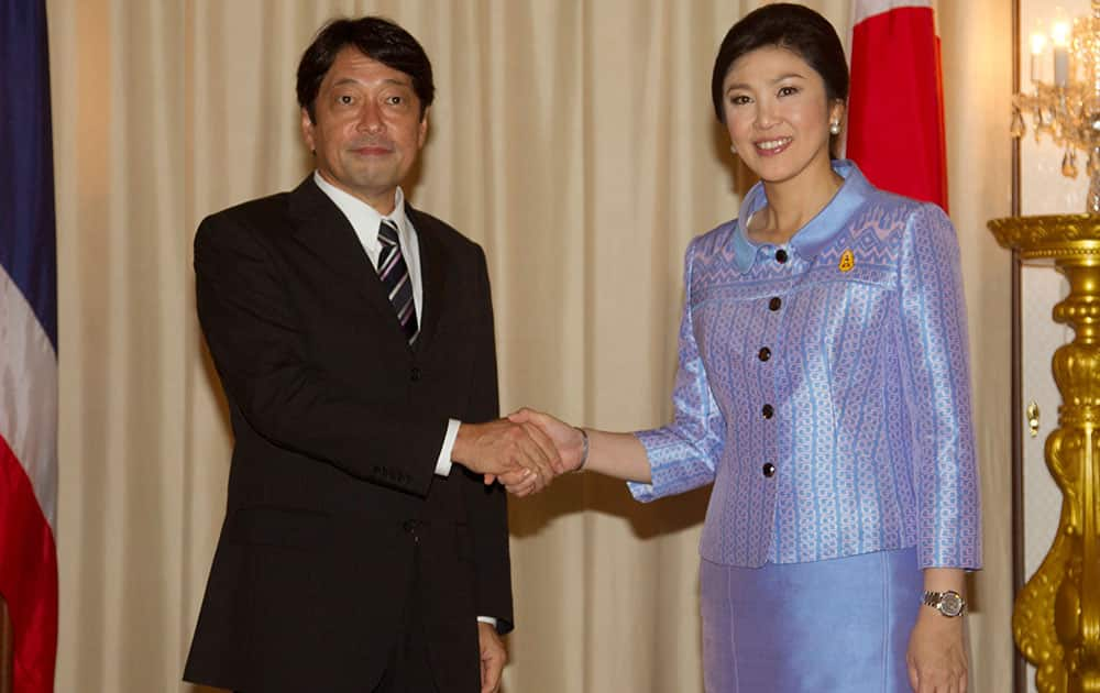 Japan`s Defense Minister Itsunori Onodera shakes hands with Thai Prime Minister Yingluck Shinawatra at Government House in Bangkok.