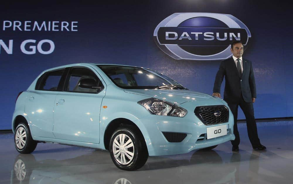 Nissan Motor Co. President and CEO Carlos Ghosn poses for photographers with a Datsun GO during its unveiling for Indonesian market in Jakarta.