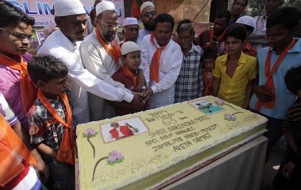 Muslim supporters of BJP prepare to cut a cake as they celebrates the birthday of Gujarat state chief minister Narendra Modi in Ahmedabad.