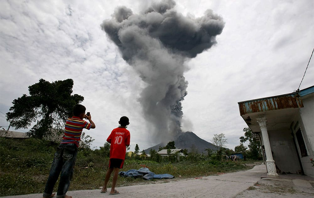 Indonesian youths watch as Mount Sinabung erupts in Karo, North Sumatra, Indonesia.