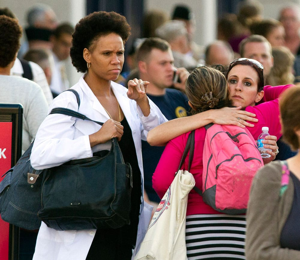 Family and friends greet staff of the Naval Sea Systems Command headquarters after they were bused from the Washington Navy Yard to Nationals Park, in Washington.