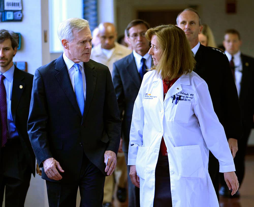 Secretary of the Navy Ray Mabus speaks with Dr. Janis M. Orlowski as they walk in the corridor at Washington Hospital Center, in Washington.