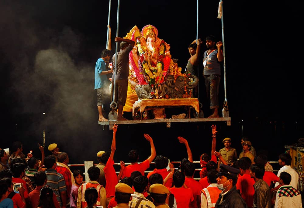 An idol of Hindu god Ganesha is lifted to be immersed in the Hussain Sagar Lake during Ganesh Chaturthi festival celebrations in Hyderabad.
