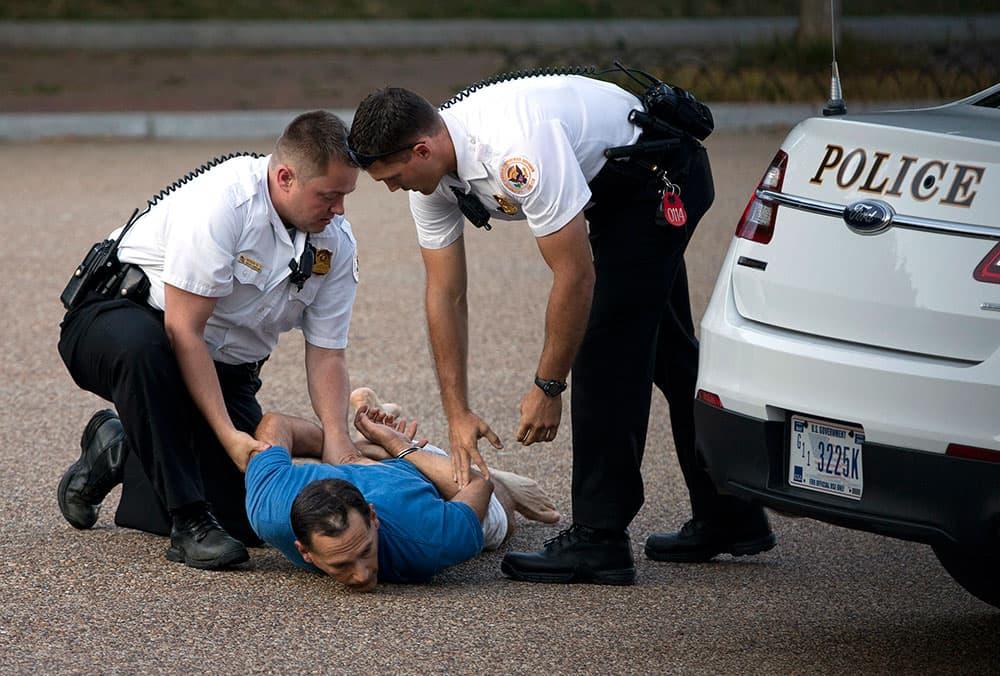 A man is taken into custody by uniformed Secret Service Police on Pennsylvania Avenue outside the White House in Washington.