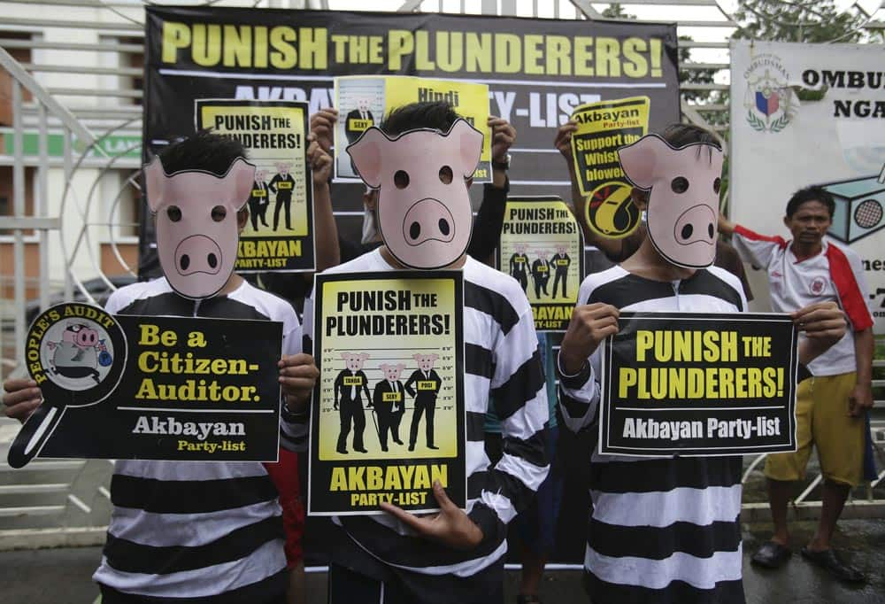Filipino protesters wear pigs masks as they hold slogans during a rally outside the Office of the Ombudsman, or the anti-graft prosecutor in suburban Quezon city, north of Manila, Philippines.
