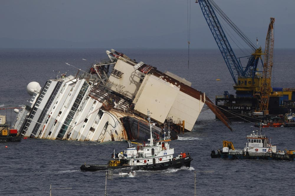 Tow boats sail past the Costa Concordia ship as it lies on its side near the Tuscan Island of Giglio, Italy.