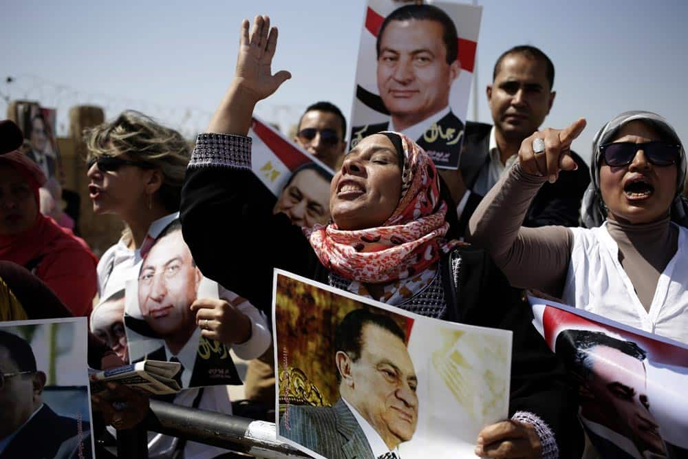 Egyptians carrying photos of ousted president Hosni Mubarak chant slogans against ousted President Mohammed Morsi and the Muslim Brotherhood as they demonstrate their support for Mubarak at a court in Cairo.
