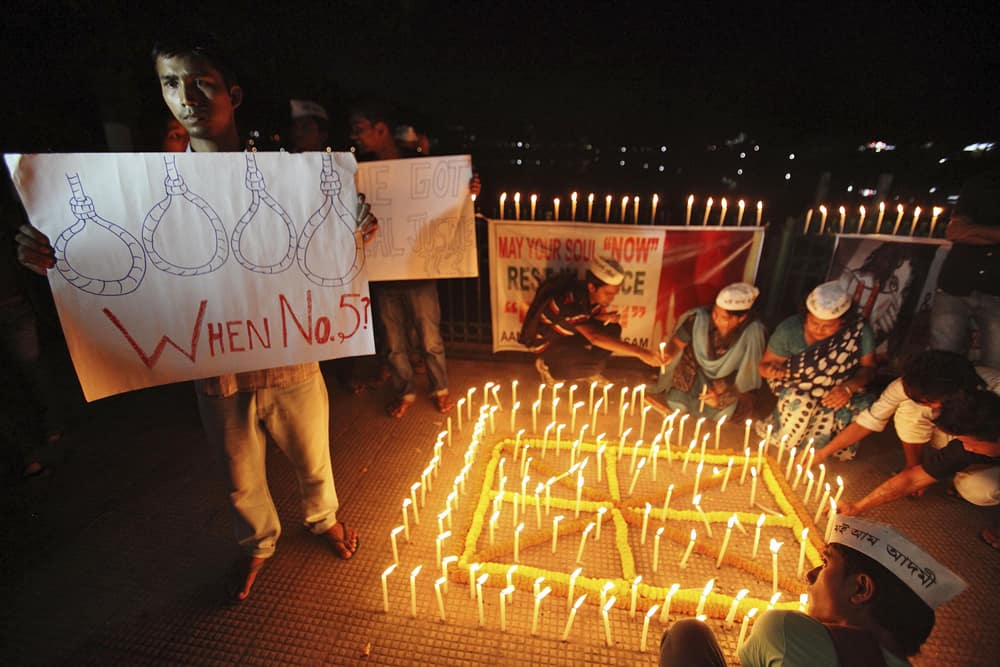 People light candles to mark the verdict after a judge pronounced death sentences for four men convicted in the rape and murder of a student on a moving bus in New Delhi last year, in Guwahati.