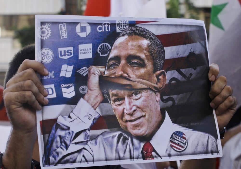 A man holds a poster depicting former US president George W. Bush putting on a mask of US President Barack Obama during a demonstration against a possible military strike in Syria, near the US Embassy in Awkar, east of Beirut, Lebanon.