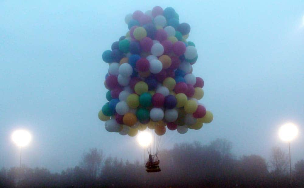 This photo provided by Mark McBreairty, a balloon cluster carrying Jonathan Trappe lifts off from Caribou, Maine.