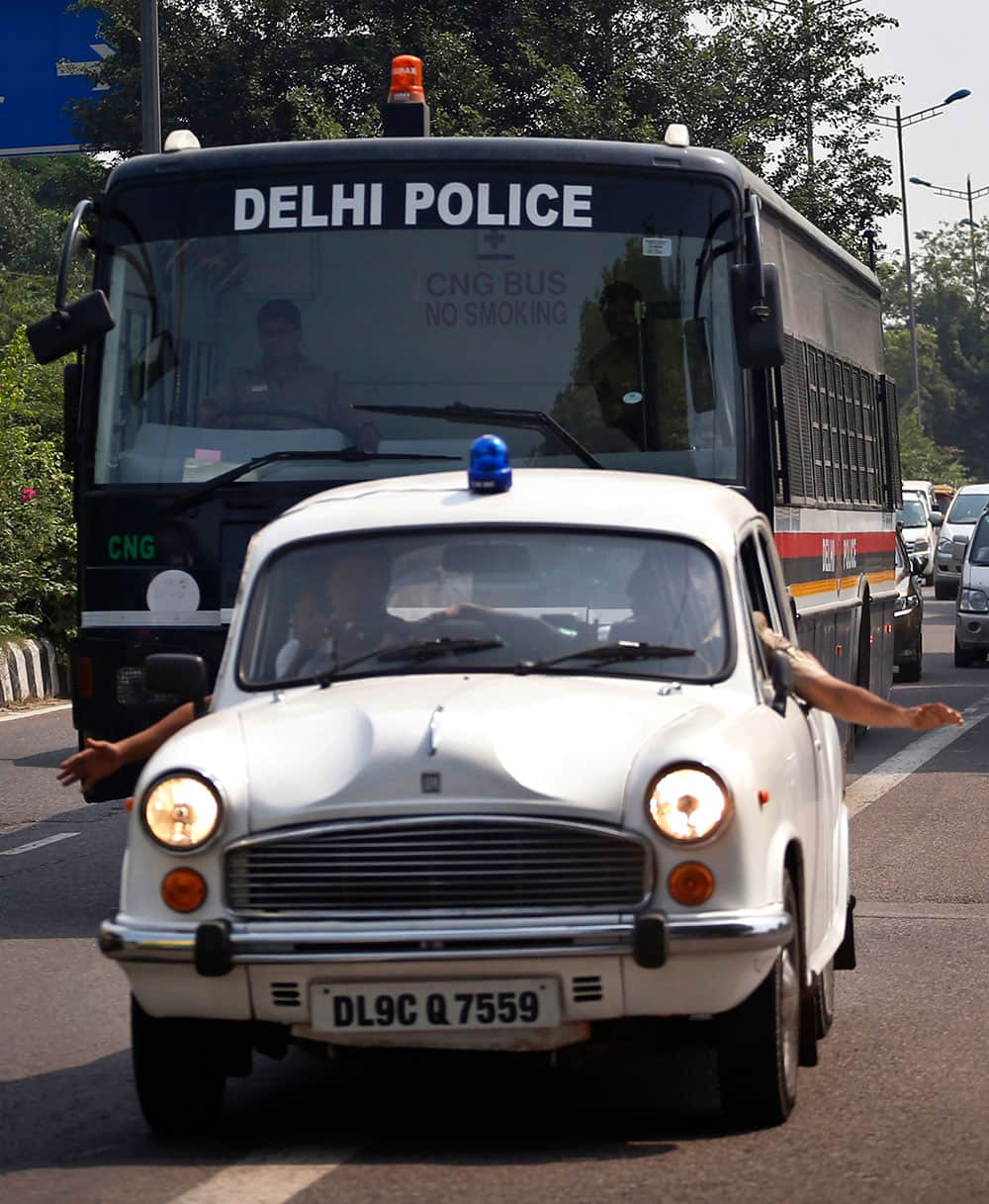 A police car clears the way for a van carrying four men convicted in the fatal gang rape of a young woman on a moving New Delhi bus last year on the way to a court complex to be sentenced, in New Delhi.
