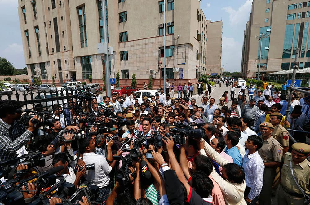 Defense lawyer A.P. Singh, center, speaks to journalists as he comes out after an Indian court convicted four men Tuesday in the fatal gang rape of a young woman on a moving New Delhi bus last year, in New Delhi, India.