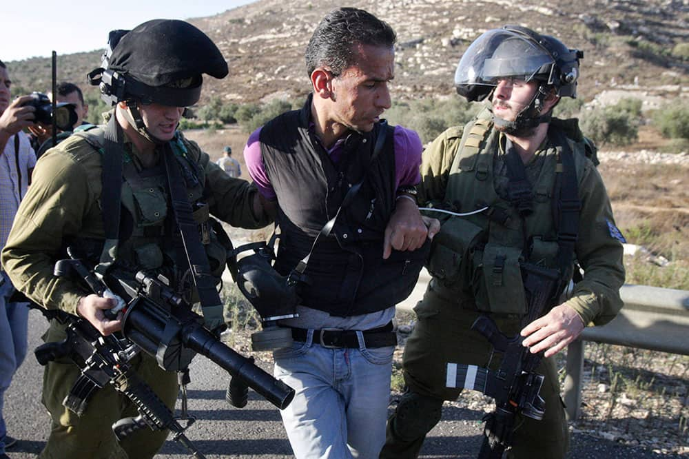 A Palestinian man is detained by Israeli soldiers during a protest near the West Bank village of Qaryout near Nablus. Palestinians protested the closure of a road to their village.