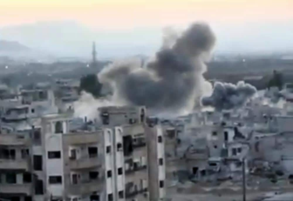 This image taken from video obtained from the Shaam News Network, which has been authenticated based on its contents and other AP reporting, smoke rises from buildings due to heavy artillery shelling in Barzeh, a district of Damascus, Syria.