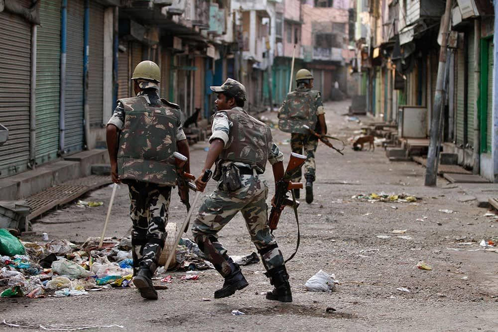 Security forces chase rioters, unseen, during an army-enforced curfew imposed following deadly clashes between Hindus and Muslims at Muzaffarnagar in Uttar Pradesh state.