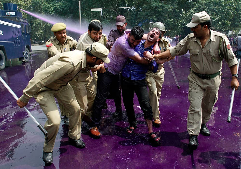 Police use colored water cannon and detain Kashmiri government employees during a protest in Srinagar.