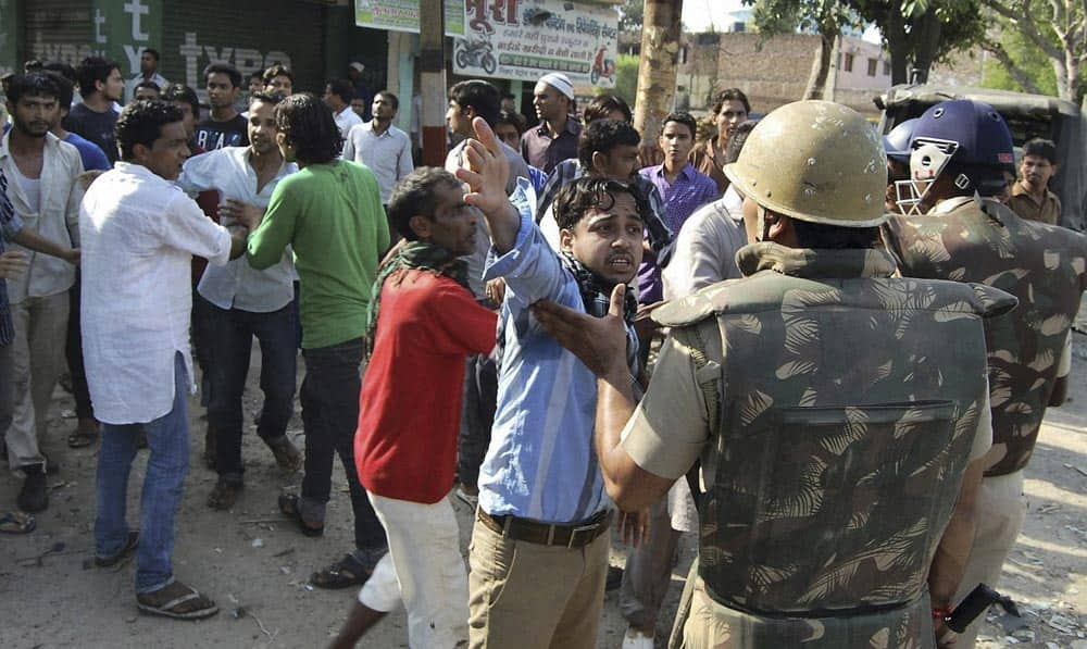 People argue with Indian policemen during curfew hours following riots and clashes between two communities in Muzaffarnagar, Uttar Pradesh.
