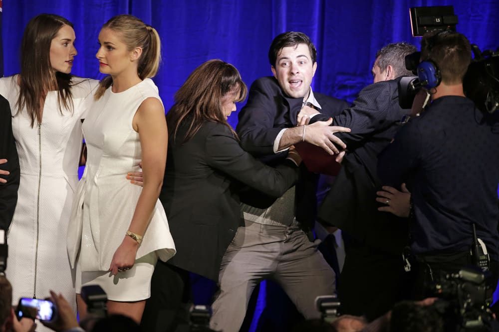 A man is forced off the stage by security as Louise Abbott and Bridget Abbott come to the stage to support their father, Tony, in Sydney following his win in Australia`s national election.