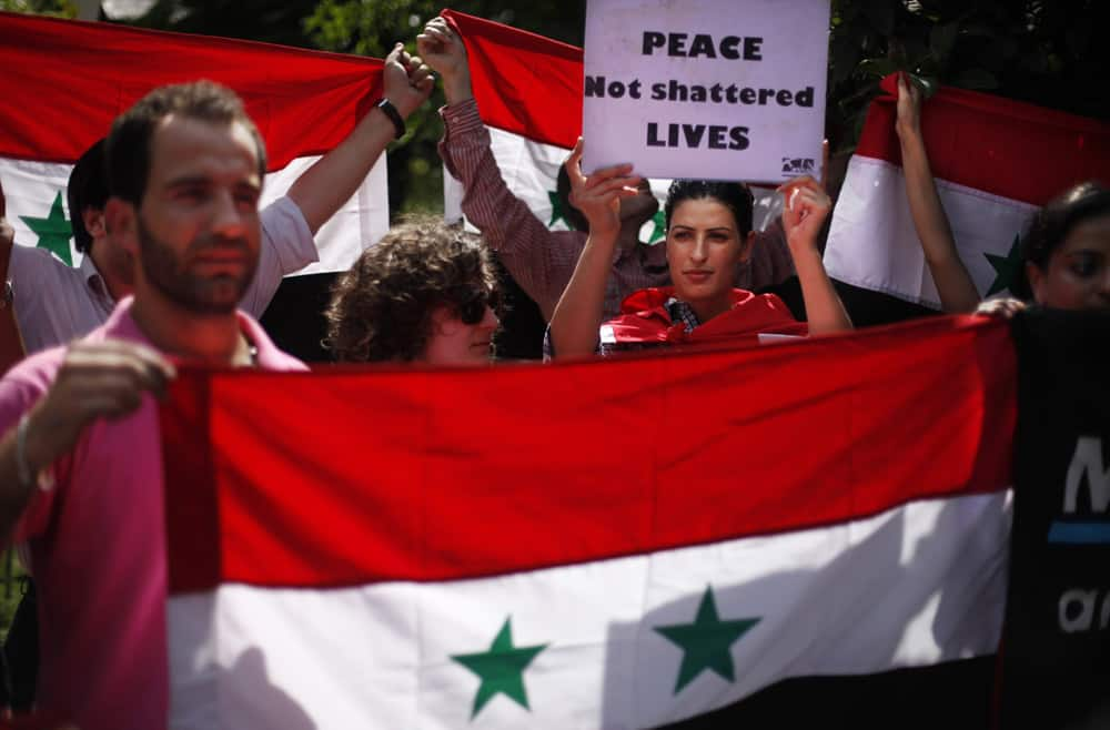 Syrians living in India hold a Syrian flag and participate in a protest march against a possible US-led attack on Syria, towards the US embassy in New Delhi.
