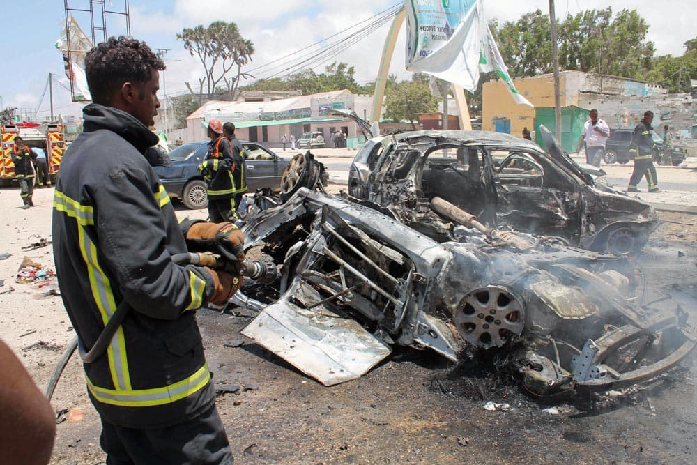 A firefighter sprays water on destroyed cars in Mogadishu, Somalia.