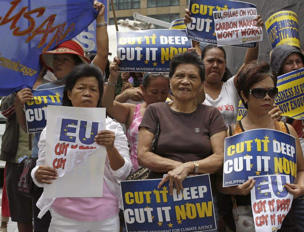 Protesters picket a posh hotel at the financial district of Makati city, east of Manila, to coincide with the visit of EU Commissioner for Climate Action Connie Hedegaard in the Philippines and to demand to increase EU targets to reduce Greenhouse gas emissions.