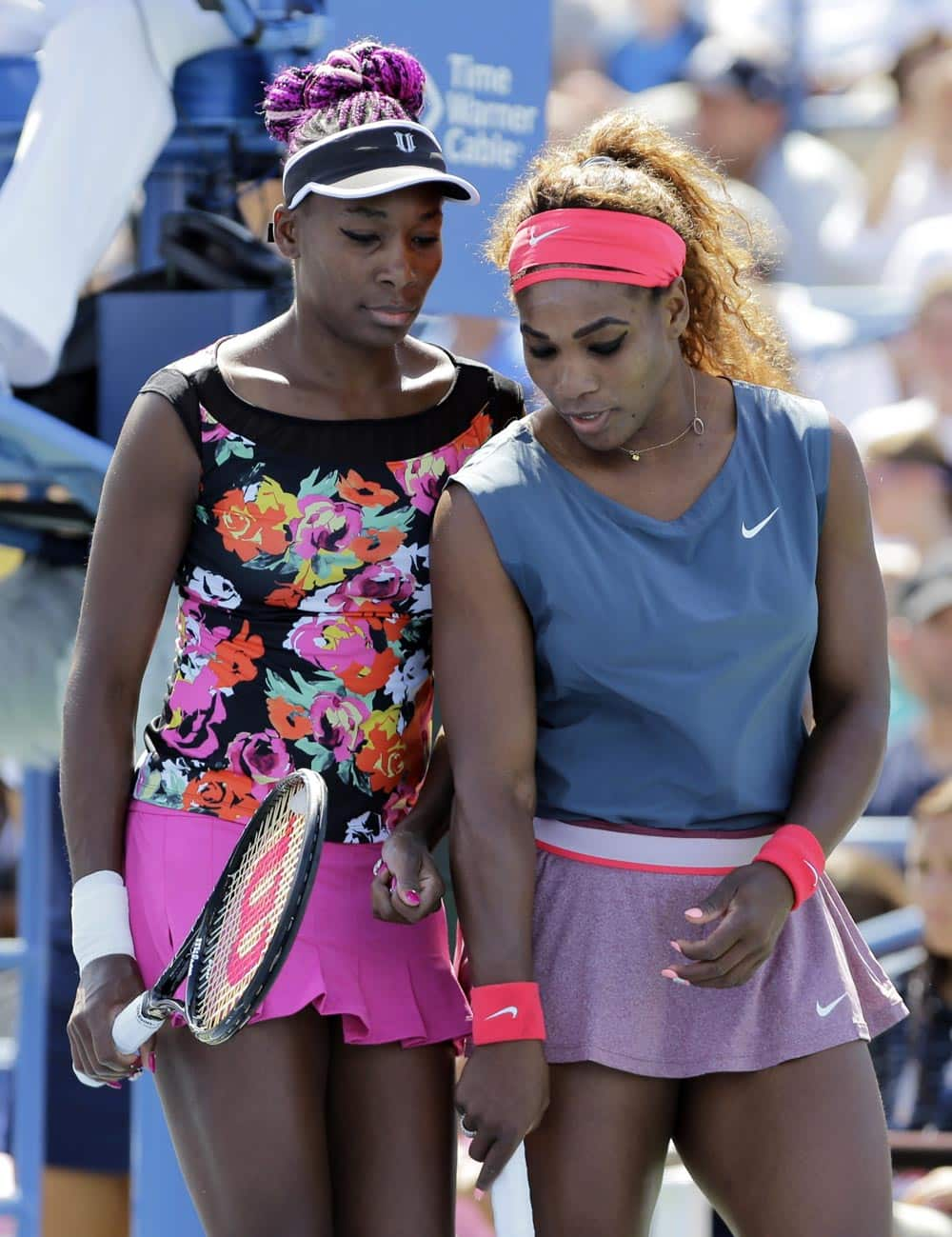 Venus Williams, left, and Serena Williams plan the next point against Sara Errani, of Italy, and Roberta Vinci, of Italy, during the women`s doubles quarterfinals of the 2013 US Open tennis tournament.
