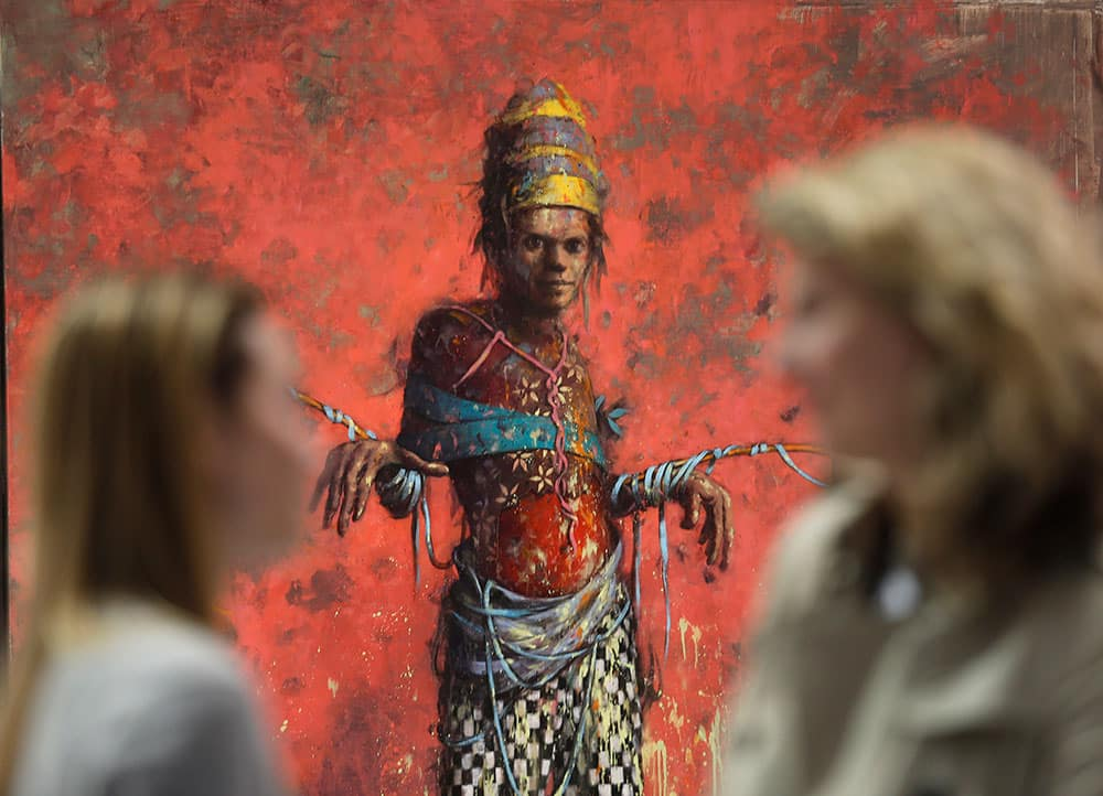 Women talk in front of a painting by Jonas Burgert from the Blain Southern gallery during a private viewing of the ART Rio-International Art Fair in Rio de Janeiro, Brazil.