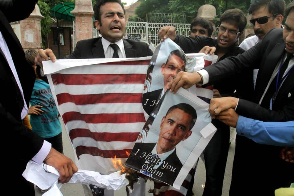 Pakistani lawyers burn representation of the US flag during an anti-American rally in Lahore.