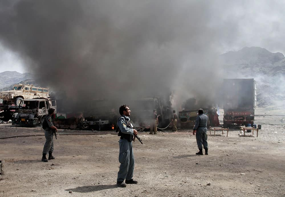 Afghan police officers watch the site of a militant attack at the Torkham area near the Pakistan-Afghanistan border as NATO supply trucks burn in Jalalabad province east of Kabul, Afghanistan.