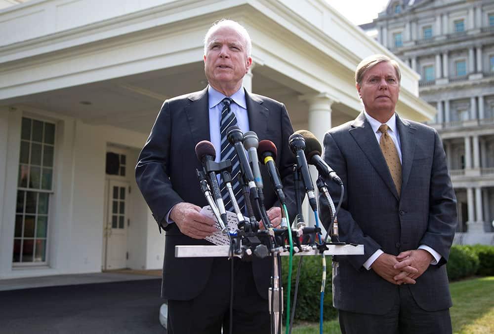 Sen. John McCain, R-Ariz., left, accompanied by Sen. Lindsey Graham, R-S.C., speaks with reporters outside the White House in Washington.