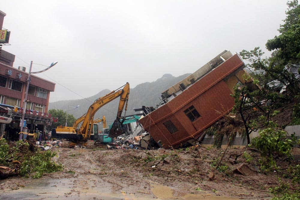 A building is seen toppled on its side from strong flooding caused by heavy rain left from Tropical Storm Kong-Rey in the northeastern town of Keelung, Taiwan.