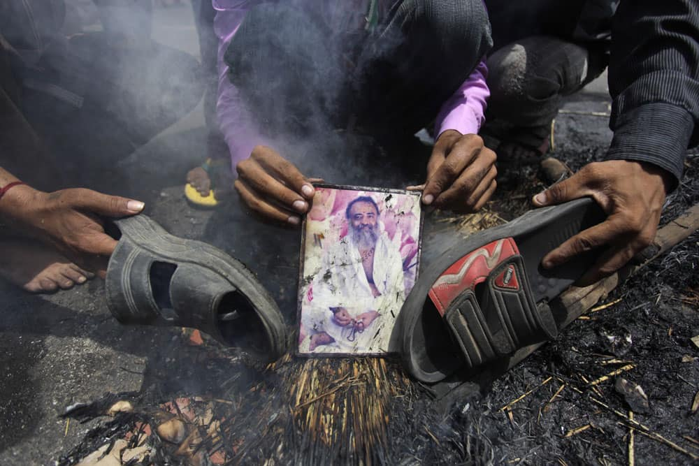 An Indian supporter of India`s ruling Congress party holds a burning photograph of Indian godman Asaram Bapu as others beat it with footwear during a protest in Ahmadabad.