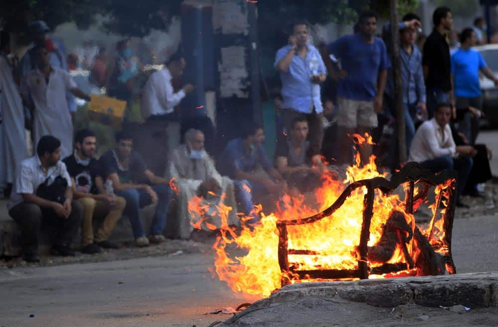 Supporters of Egypt`s ousted President Mohammed Morsi, rest on the roadside behind a burning sofa during a protest in Cairo, Egypt.