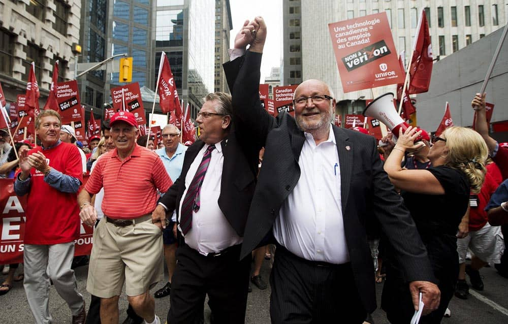 Canadian Auto Workers` president Ken Lewenza, left, and Communications, Energy and Paperworkers Union of Canada president Dave Coles attend a protest against Verizon Wireless coming to Canada during a rally in Toronto.