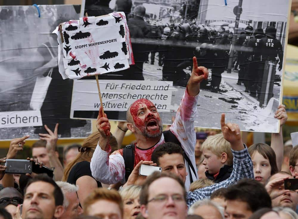 A protestor demonstrates against the export of weapons during an election rally of German Chancellor Angela Merkel in Frankfurt, Germany.
