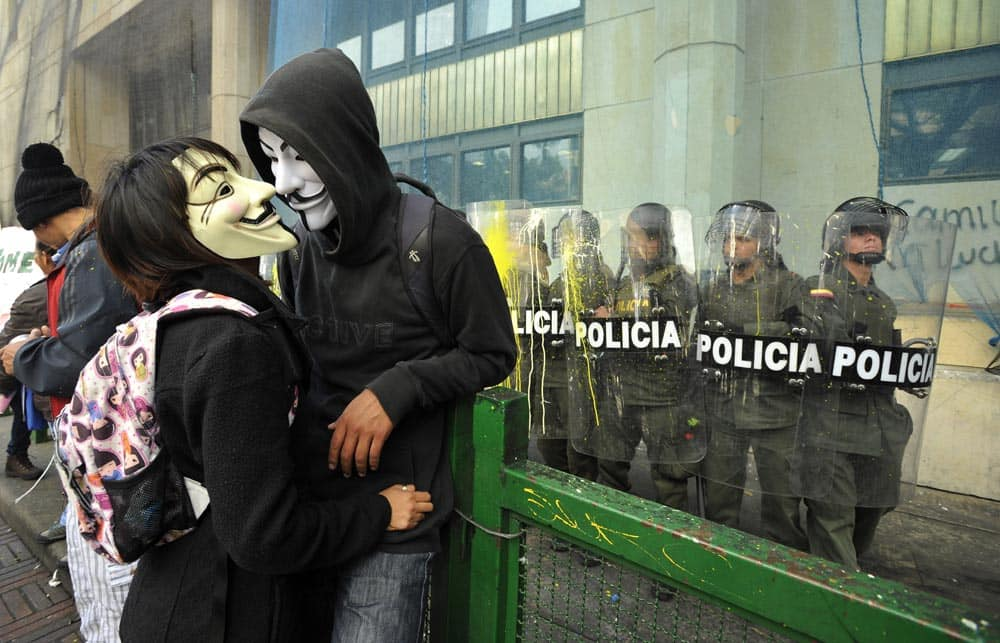 A couple of masked protesters stand near riot police guarding a public building during a rally in Bogota, Colombia.