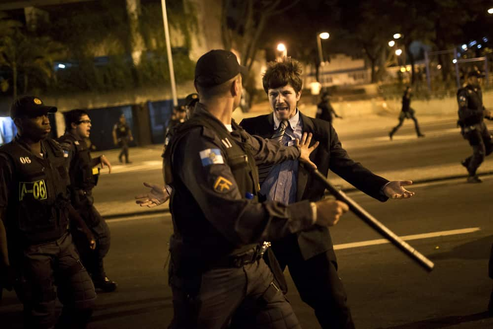 A police officer pushes back a man complaining about the detention of protesters near Guanabara Palace, the office of Rio de Janeiro Governor Sergio Cabral in Rio de Janeiro, Brazil.