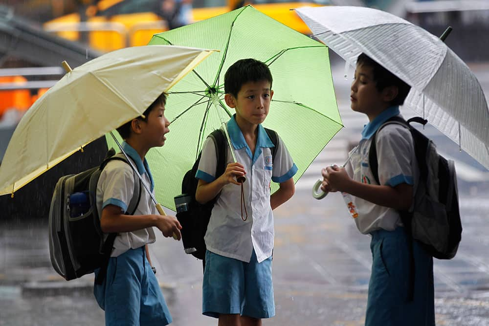 School boys ride out heavy rains from passing Tropical Storm Kong-Rey in Taipei, Taiwan. Tropical Storm Kong-Rey battered Taiwan on Thursday, dumping more than 500 mm (19 inches) of rain on the heavily populated west coast amid widespread flooding.