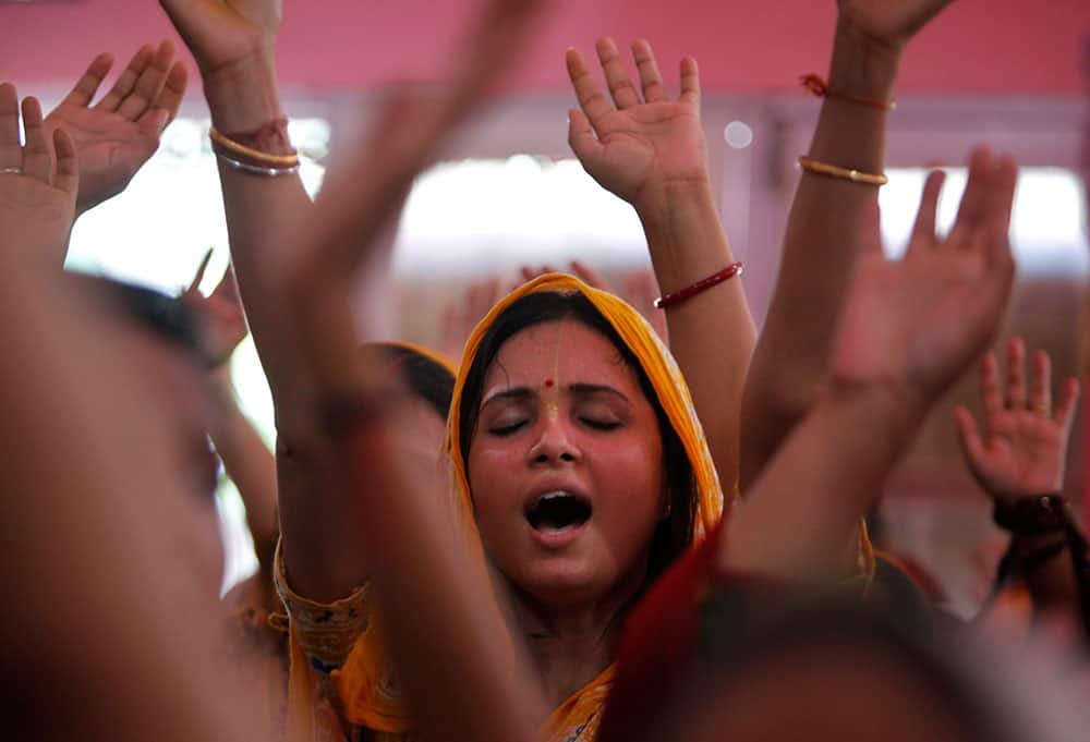Hindu devotees dance as they worship Lord Krishna as part of Janamashtami celebrations at the ISKON temple in Jammu.