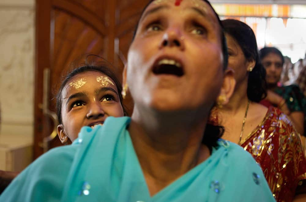Devotees react as they look at wall paintings at the ISKON temple, a famous Hindu temple of Lord Krishna and Radharani, during Janmashtami in New Delhi.