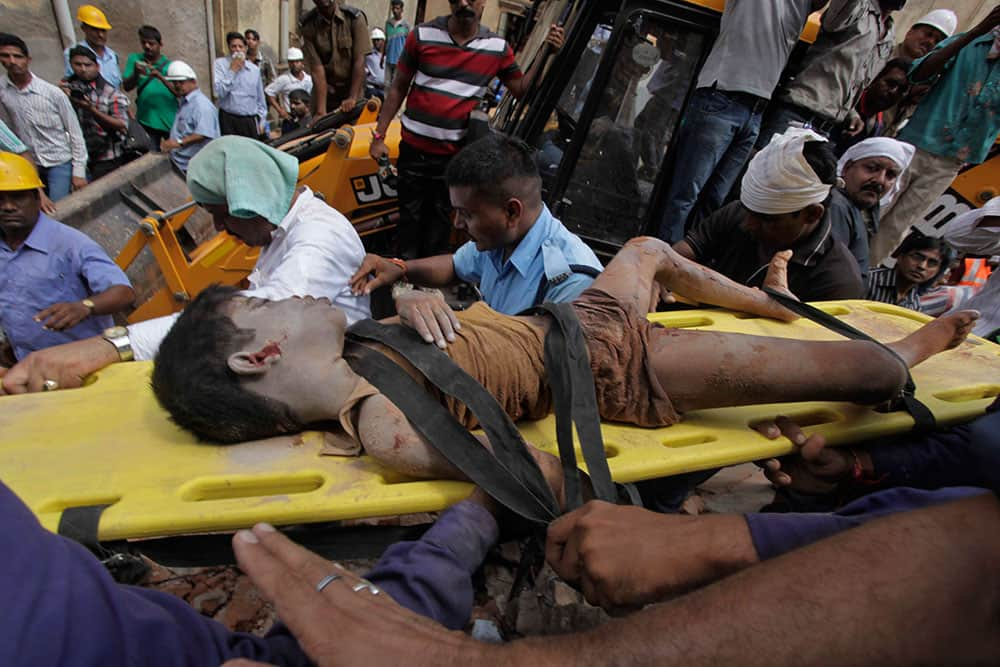 Rescuers carry the body of a victim they pulled out after two adjacent apartment buildings collapsed at Vadodara in Gujarat state, India.