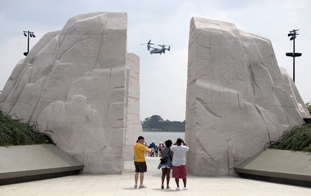 A Osprey military helicopter flies by the Martin Luther King Jr. Memorial in Washington.