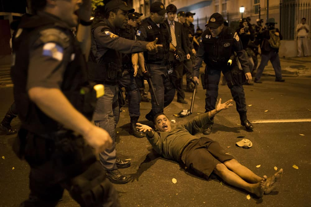 A man complains about being hit by police after falling to the ground during a protest near Guanabara Palace, the office of Rio de Janeiro Governor Sergio Cabral in Rio de Janeiro.