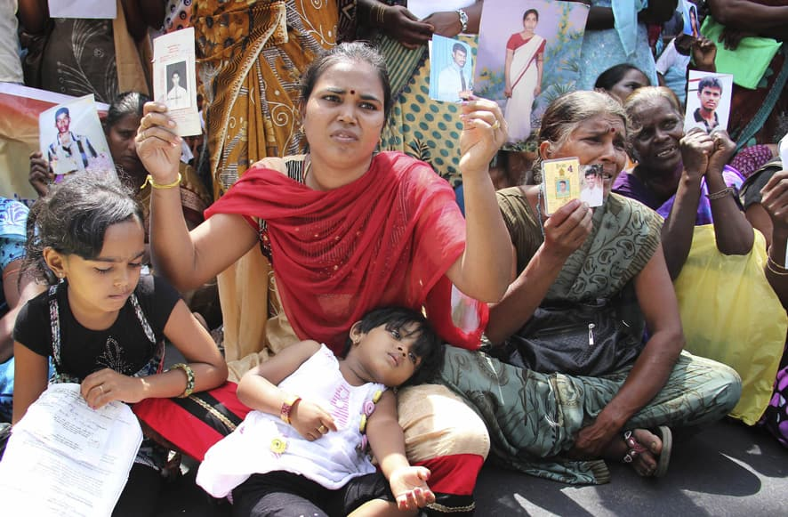 Family members of disappeared Tamil people holding pictures of their relatives protest during the visit of U.N. High Commissioner for Human Rights Navi Pillay, in Jaffna, Sri Lanka.