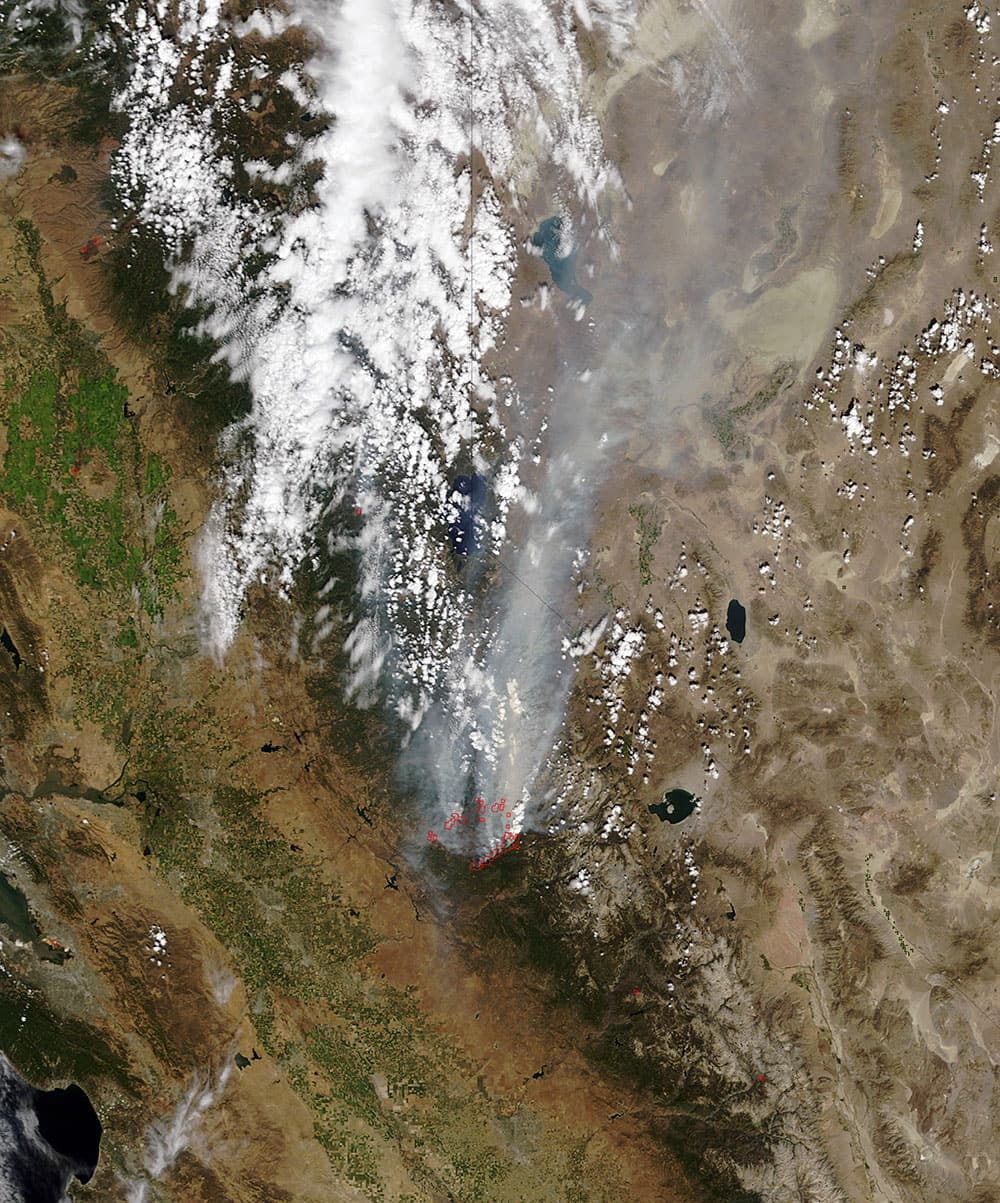 This satellite photo released by NASA, a smoke plume trails north from the drought-fueled Rim Fire, center, burning near Yosemite National Park in central California. Red outlines indicate hot spots where the satellite detected unusually warm surface temperatures associated with fires.