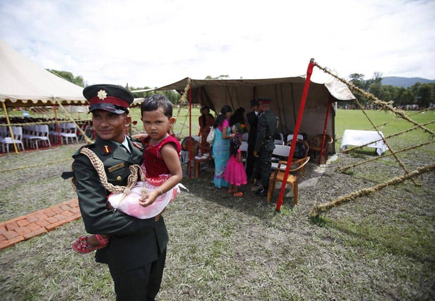 A former Maoist rebel carries his daughter during a ceremony at Nepalese Military Academy in Kharipati, Nepal.