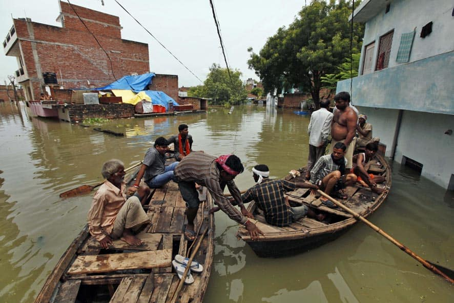 People on boats try to reach a safer ground after the overflowing of the Ganges River following heavy monsoon rains in Salori.