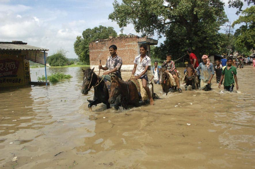 Laborers wade through flood waters in Mirzapur, Uttar Pradesh state.